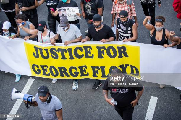 Protesters carry a banner that says Justice for George Floyd as they made their way across the Brooklyn Bridge Thousands of protesters walked from...