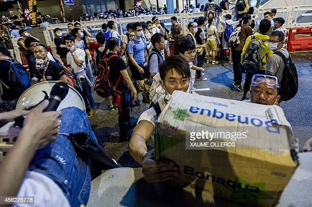 Protesters carry a box of water bottles to be distributed to fellow demonstrators during a prodemocracy protest in Hong Kong on September 28 2014...