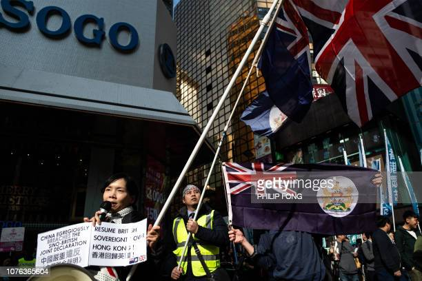 Protesters carry a British Union Jack flag and Hong Kong's former colonial flag during the annual New Year's Day prodemocracy rally in Hong Kong on...
