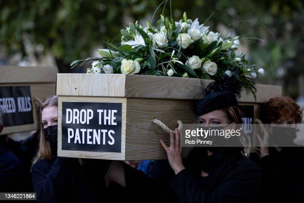 """Protesters carry a cardboard coffin which reads """"DROP THE PATENTS"""" through Parliament Square during a protest against Covid-19 vaccine patents on..."""