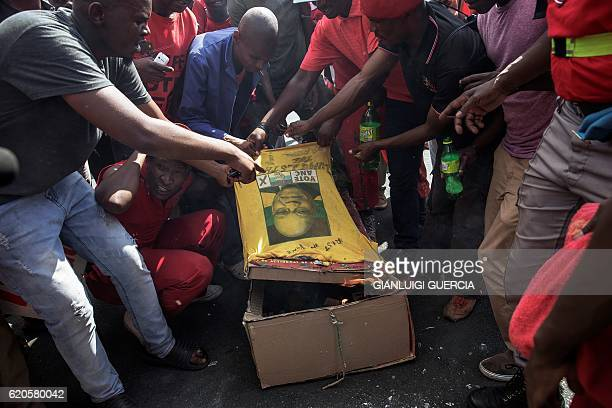 Protesters carry a cardboard mock up coffin with the picture of South African President Jacob Zuma as Members and supporters of the South African...
