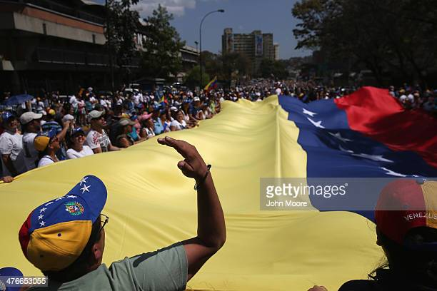 Protesters carry a giant Venezuelan flag while marching in an antigovernment demonstration on March 4 2014 in Caracas Venezuela Meanwhile workers...