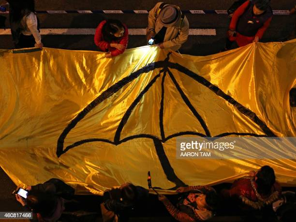 Protesters carry a long yellow banner during a march with an umbrella a recent symbol of Hong Kong's democracy movement painted on it during a march...
