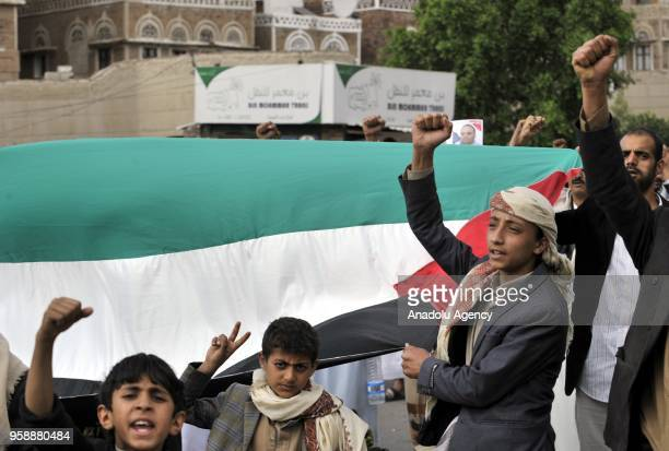 Protesters carry a massive Palestinian flag at Bab alYaman street during a protest against United States' plans to relocate the US Embassy from Tel...