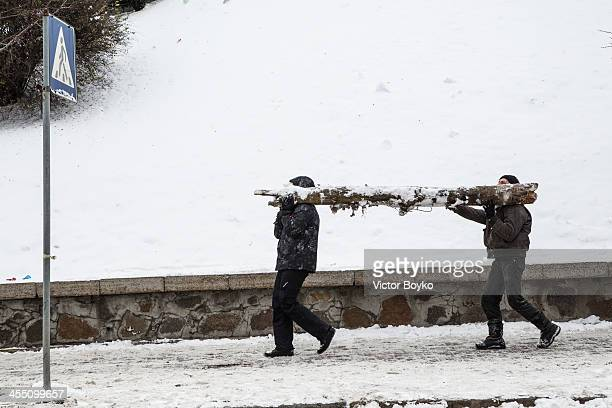 Protesters carry a piece of wood for reinforcing barricades on Independence Square on December 11 2013 in Kiev Ukraine Riot police today tried to...