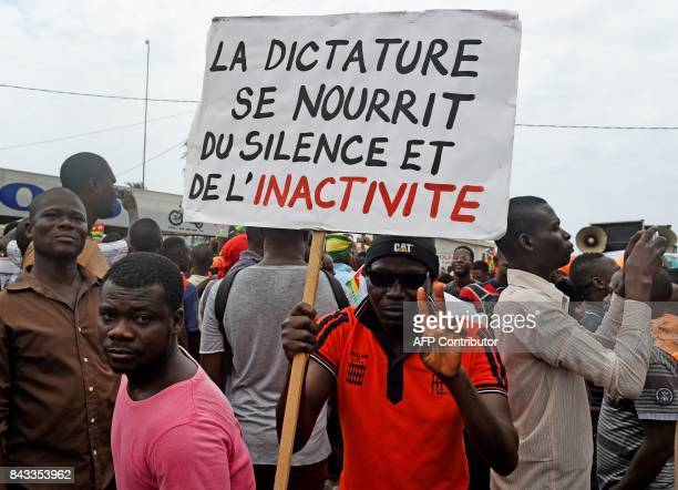 Protesters carry a placard which translates as 'dictatorship feeds on silence and inactivity' while they march shouting slogans as they call for...