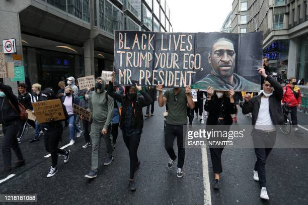 Protesters carry a placard with a picture of George Floyd as they march back in to central London after attending a demonstration outside the US...