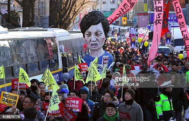 Protesters carry an effigy of South Korea's President Park Geun-Hye during a rally demanding her arrest near the presidential house in Seoul on...