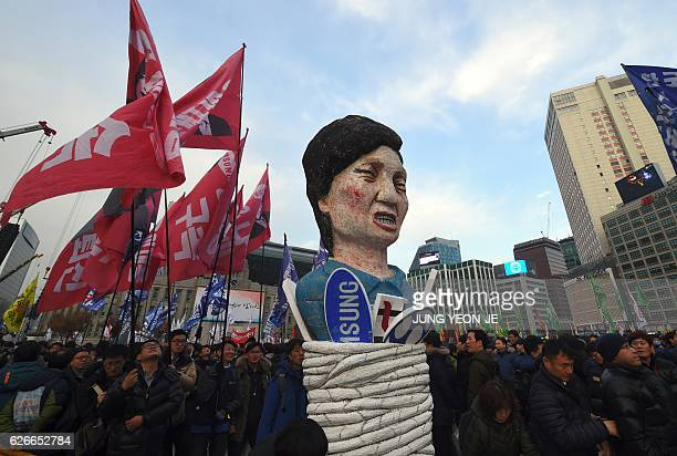 TOPSHOT Protesters carry an effigy of South Korea's President Park GeunHye during an antigovernment rally demanding the resignation of the president...