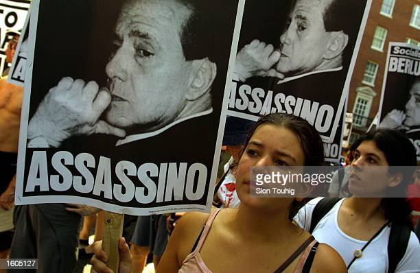 Protesters carry banners accusing Italian President Sylvio Berlusconi of murder July 28 2001 at a demonstration outside the Italian embassy in London...