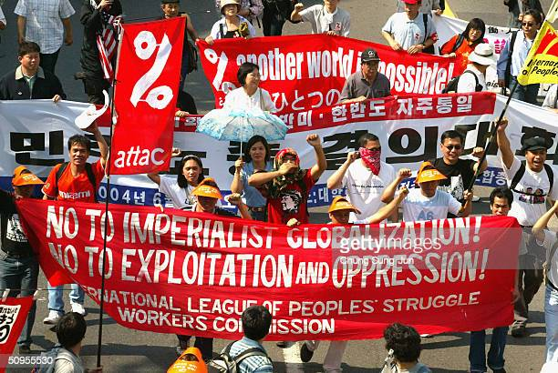 Protesters carry banners and placards during a rally against a meeting of the World Economic Forum near the Shilla Hotel where the Geneva...