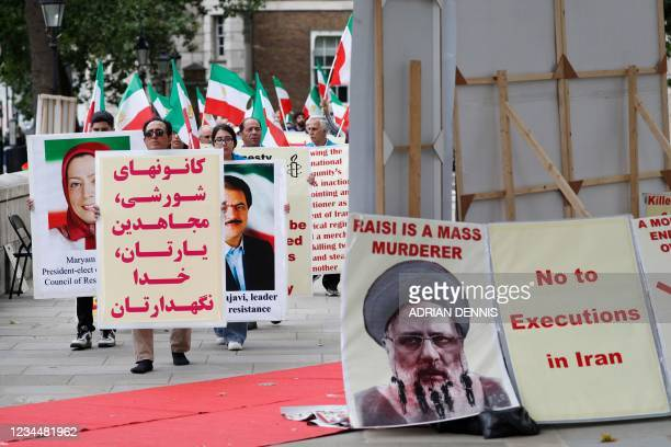 Protesters carry banners during a demonstration organised by supporters of the National Council of Resistance of Iran to protest against the...