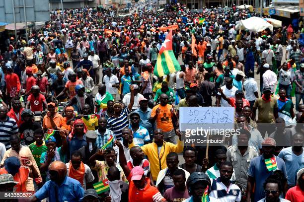 Protesters carry flags and placards while they march shouting slogans as they call for reforms during an antigovernment rally in Lome on September 6...