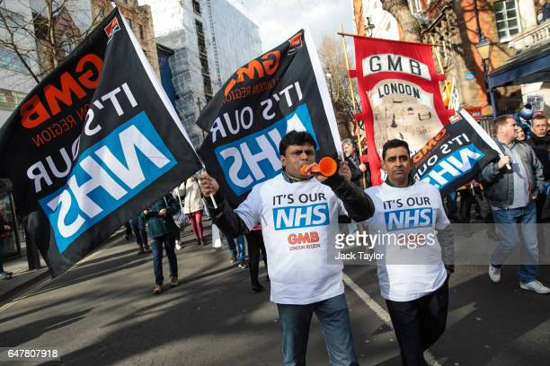 Protesters carry flags through central London during a demonstration in support of the NHS on March 4 2017 in London England Thousands march from...