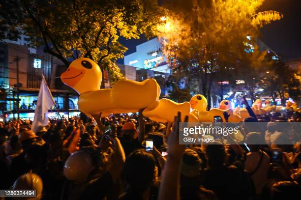 Protesters carry inflatable yellow rubber ducks at the Ratchaprasong Intersection on November 18, 2020 in Bangkok, Thailand. Pro-democracy protesters...