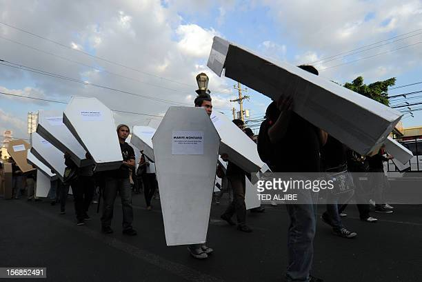 Protesters carry mock coffins during a march protest to Malacanang Palace in Manila on November 23 to commemorate the third anniversary of the...