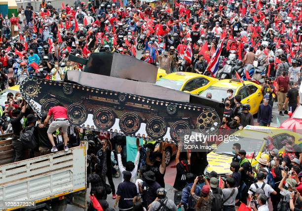 Protesters carry out a mockup of a tank from a truck during a car mob demonstration. More than 1,000 cars and motorcycles set off from Asoke...