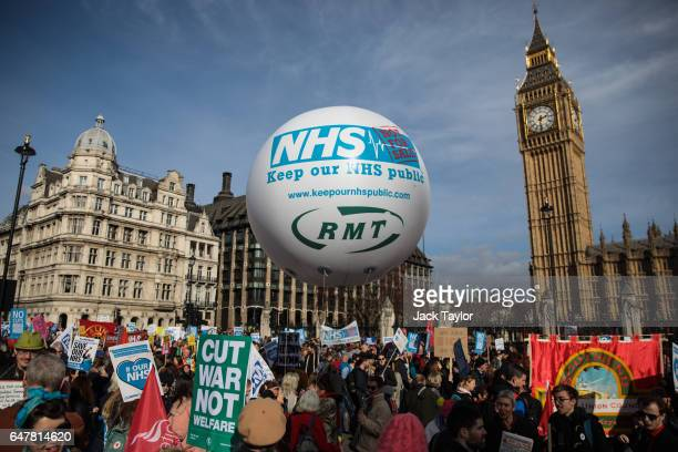 Protesters carry placards and a balloon as they arrive in Parliament Square during a demonstration in support of the NHS on March 4 2017 in London...