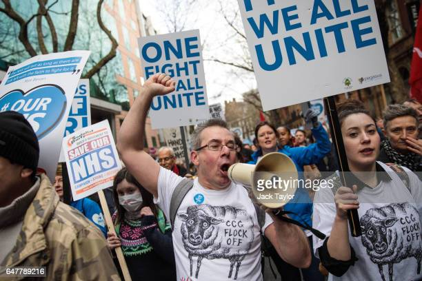 Protesters carry placards and chant as they march through central London during a demonstration in support of the NHS on March 4 2017 in London...