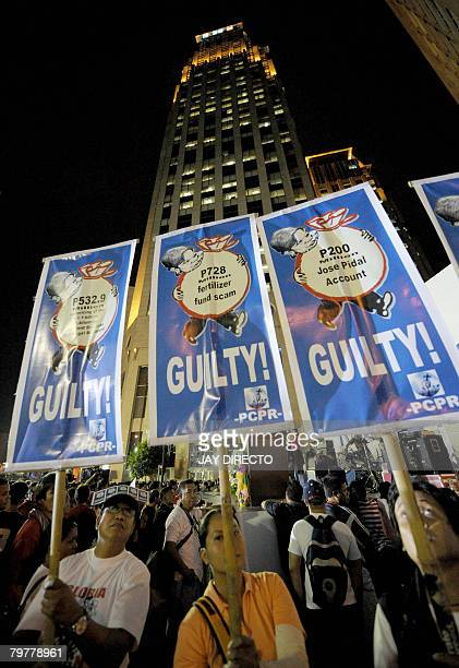 Protesters carry placards as they march in Manila's financial district of Makati on February 15 during a demonstration demanding the ouster of...