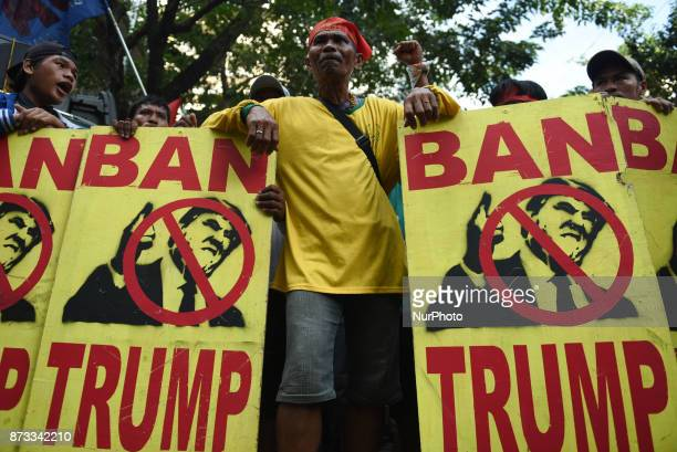 Protesters carry placards containing the image of US President Donald Trump as they try to get past antiriot police in their attempt to march towards...