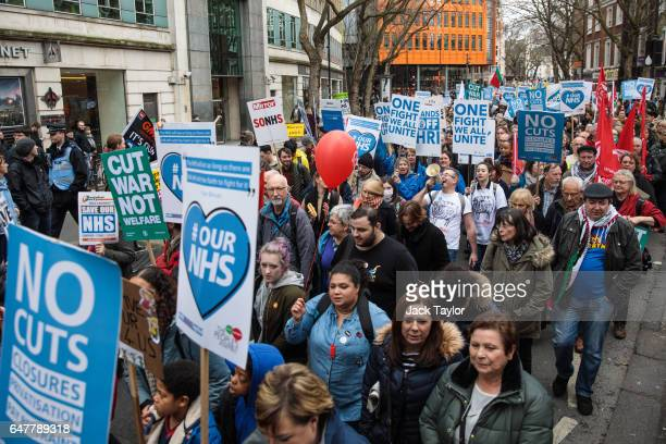Protesters carry placards through central London during a demonstration in support of the NHS on March 4 2017 in London England Thousands march from...