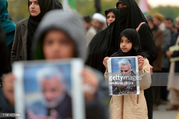 TOPSHOT Protesters carry posters with the image of top Iranian commander Qasem Soleimani who was killed in a US airstrike in Iraq during a...