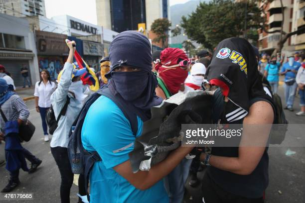 Protesters carry rocks to throw at national guard troops following an antigovernment demonstration on March 2 2014 in Caracas Venezuela Venezuela has...