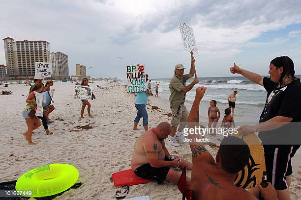 Protesters carry signs as they express themselves about the BP oil company while walking along Pensacola Beach where oil globs have come ashore as...