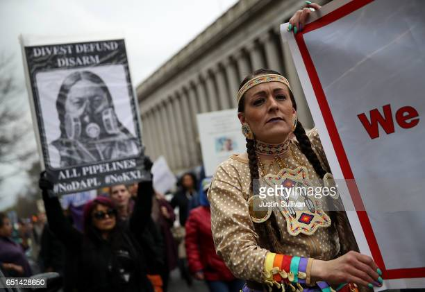 Protesters carry signs as they march during a demonstration against the Dakota Access Pipeline on March 10 2017 in Washington DC Thousands of...