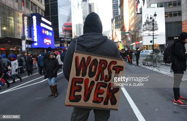 Protesters carry signs during a march on Martin Luther King Jr Day in Times Square called Rally Against Racism Stand Up for Haiti and Africa in New...