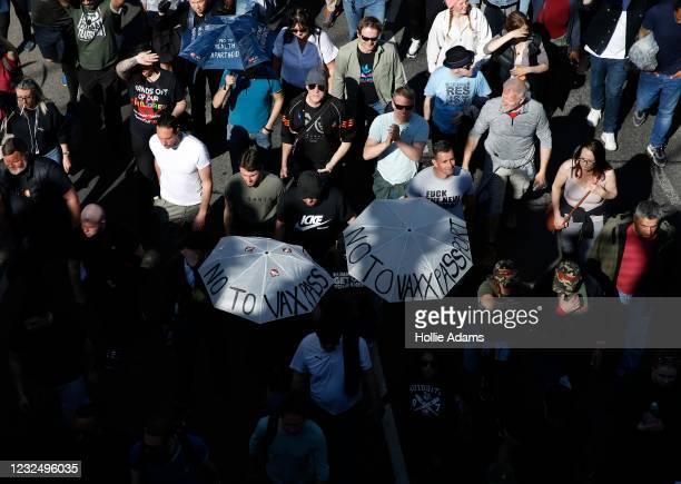 """Protesters carry umbrellas saying """"No to Vaxx Passport"""" during a """"Unite For Freedom"""" anti-lockdown demonstration held to protest against the use of..."""