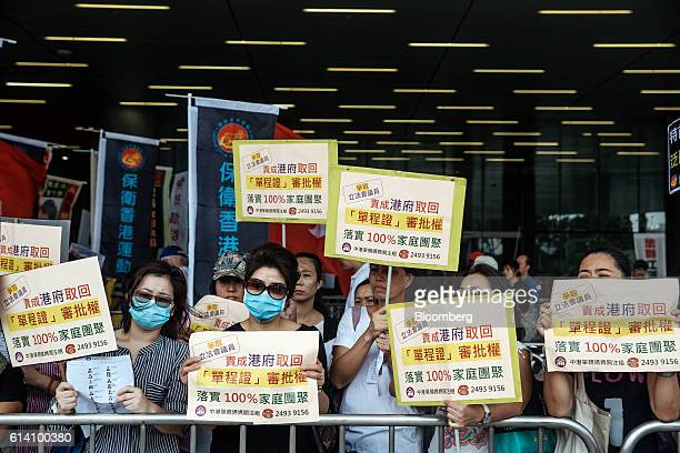 Protesters carrying banners gather ahead of an oathtaking ceremony at Hong Kong's Legislative Council in Hong Kong China on Wednesday Oct 12 2016...