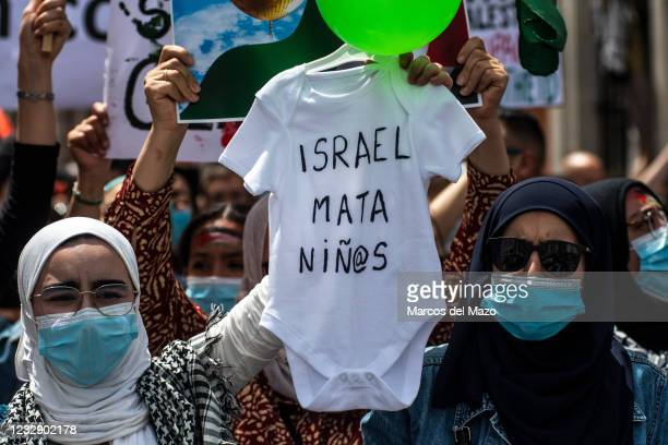 Protesters carrying children's clothing with the words 'Israel kills children' during a demonstration against the last attacks by Israel to...