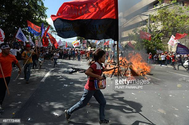 Protesters carrying flags from local organisations run past a fire after an effigy of an American eagle was set alight during a demonstration against...