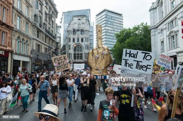 Protesters cary a big gold poster shaped as a fist with the middle finger during Together Against Trump march through central London followed by a...