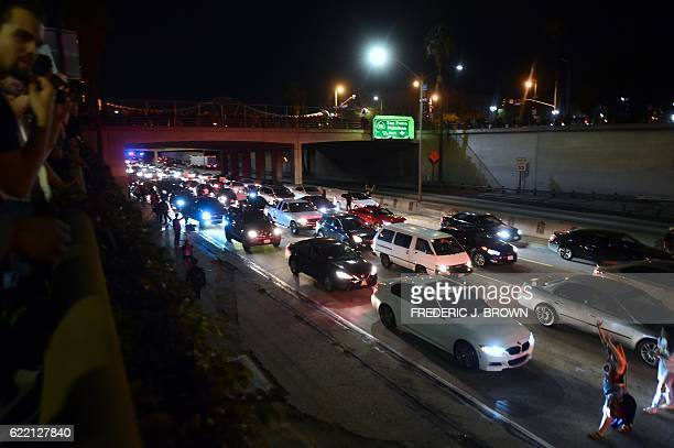 Protesters cause a chaotic traffic situation with the shutdown of a freeway in downtown Los Angeles California late on November 9 2016 as protesters...