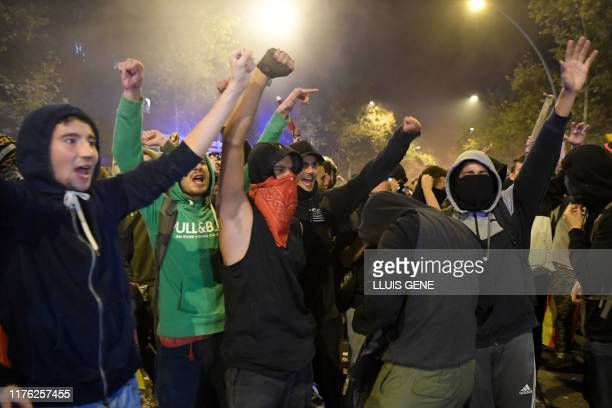 Protesters celebrate after police retreated during a demonstration called by the local Republic Defence Committees in Barcelona on October 16 after...