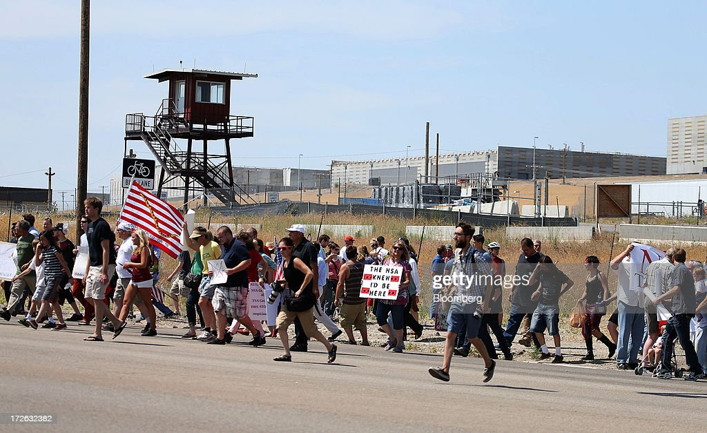 Protesters chant and sing songs at the entrance of the National Security Agency (NSA) Utah Data Center being built in Bluffdale, Utah, U.S., on Thursday, July 4, 2013. Russian President Vladimir Putin said NSA whistleblower Edward Snowden must quit hurting American interests if he wants to remain in Russia, after an official said the fugitive applied for asylum there. Photographer: George Frey/Bloomberg via Getty Images