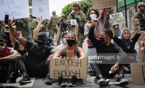 Protesters chant as National Guard troops keep watch during a peaceful demonstration over George Floyd's death on Sunset Boulevard in Hollywood on...