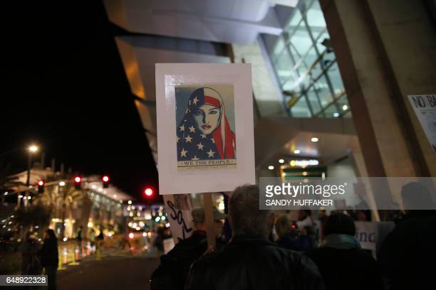 TOPSHOT Protesters chant during a rally against the travel ban at San Diego International Airport on March 6 2017 in San Diego California US...