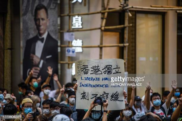 Protesters chant slogans and hold a placard during a rally against a new national security law in Hong Kong on July 1 on the 23rd anniversary of the...