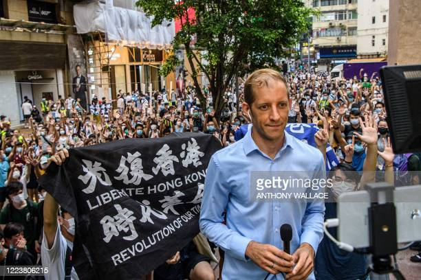 Protesters chant slogans and hold up flags as they stand behind a reporter speaking to the camera during a rally against a new national security law...