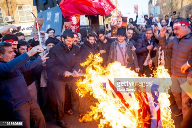Protesters chant slogans and hold up posters of Gen. Qassem Soleimani while burning representations of British and Israeli flags, during a...