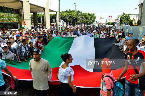Protesters chant slogans and wave a giant Palestinian flag as they march in a demonstration in the Moroccan capital Rabat on June 23 2019 against the...