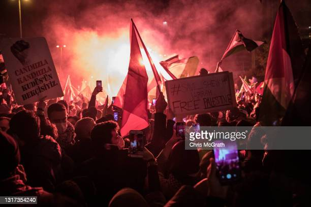 Protesters chant slogans and wave flags outside the Israeli Consulate during a protest against Israel on May 10, 2021 in Istanbul, Turkey. Tensions...