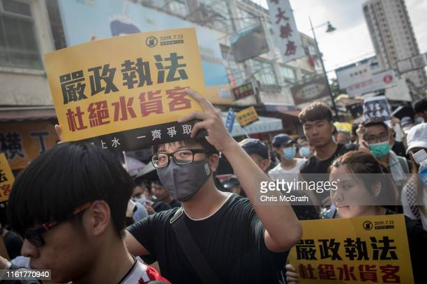 Protesters chant slogans as they march during a protest against mainland Chinese parallel traders in the Sheung Shui district on July 13 2019 in Hong...