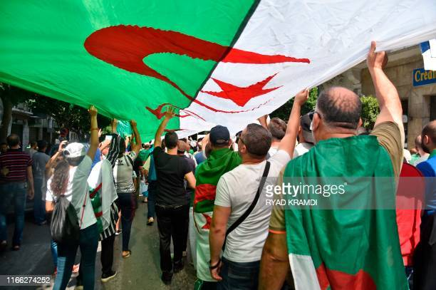 Protesters chant slogans as they march with Algerian national flags during a demonstration against the ruling class in the capital Algiers on...
