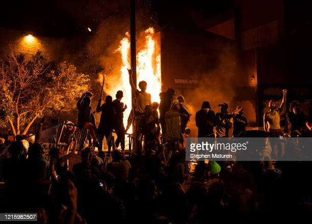 Protesters cheer as the Third Police Precinct burns behind them on May 28, 2020 in Minneapolis, Minnesota. As unrest continues after the death of...
