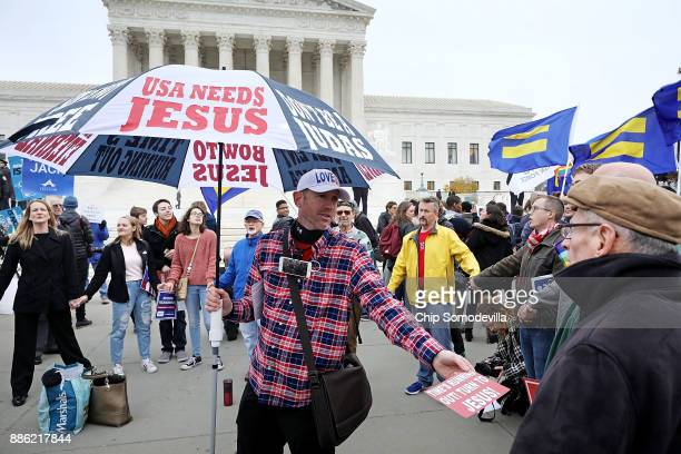 """Protesters circle around an evangelical Christan demonstrator and sing 'We Shall Overcome"""" in front of the Supreme Court building on the day the..."""